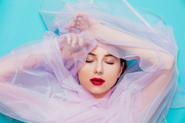 Young woman with pink tulle on blue background