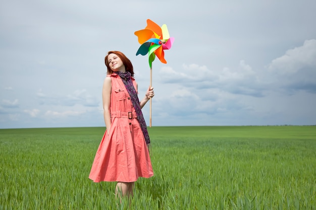 Young woman with pinwheel toy on green wheat field