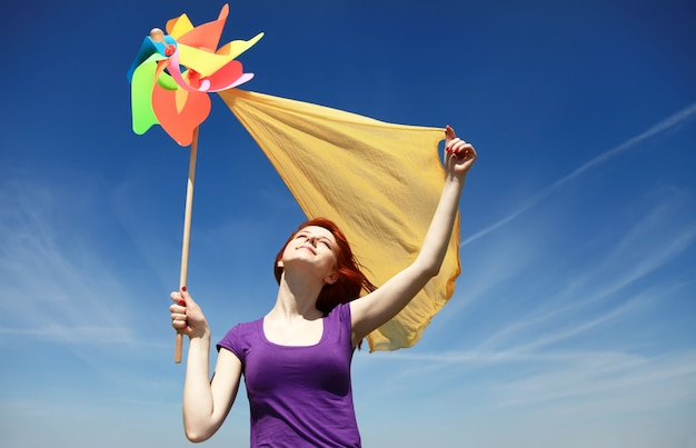 Young woman with pinwheel toy on sky background