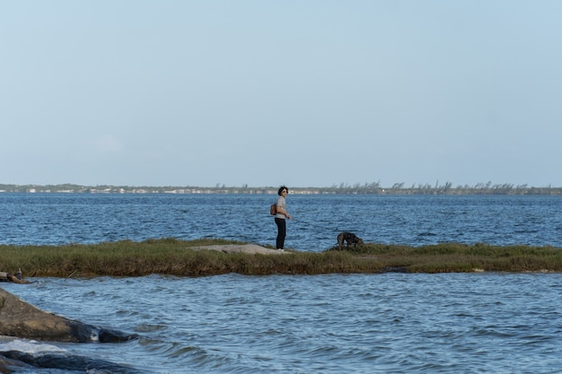 Young woman with the pit bull dog walking along a stretch of land and grass in the middle of the araruama lagoon in rio de janeiro.