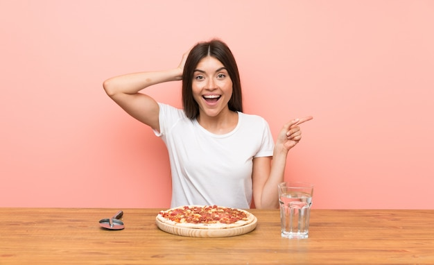 Young woman with a pizza surprised and pointing finger to the side
