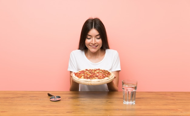 Young woman with a pizza in a table