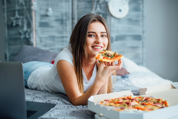 Young woman with pizza using laptop while resting on bed at home.