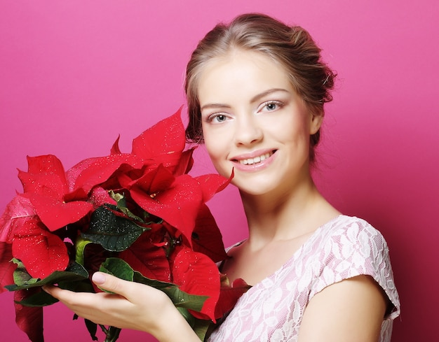 Young woman with poinsettia over pink