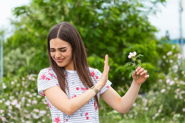 Young woman with pollen allergy holding a flower and saying no