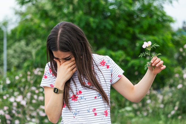 Young woman with pollen allergy holding a flower and saying no..