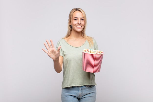 Young woman with a pop corns bucket smiling and looking friendly, showing number five or fifth with hand forward, counting down