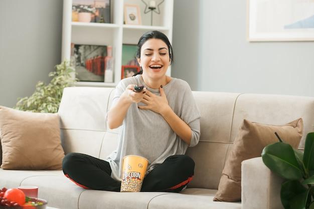 Giovane donna con il secchio di popcorn che tiene il telecomando della tv alla telecamera seduta sul divano dietro il tavolino da caffè in soggiorno