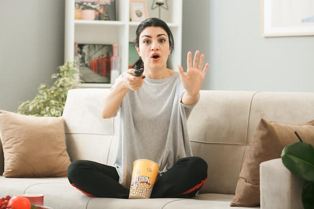 팝콘 양동이를 가진 젊은 여성이 거실에 있는 커피 테이블 뒤에 소파에 앉아 카메라에 리모컨을 들고 있습니다.