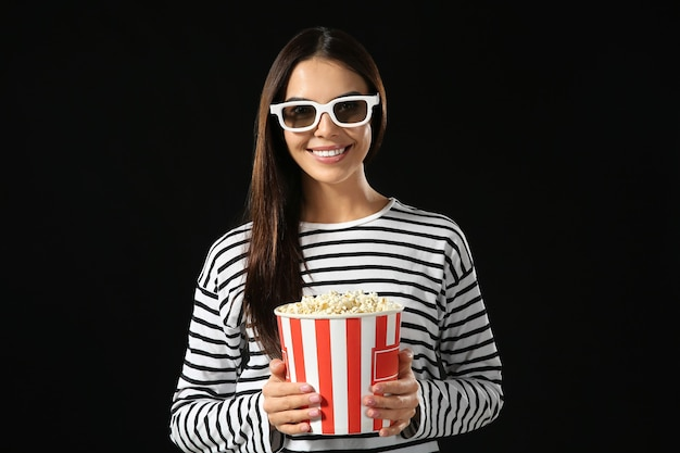 Young woman with popcorn on dark background