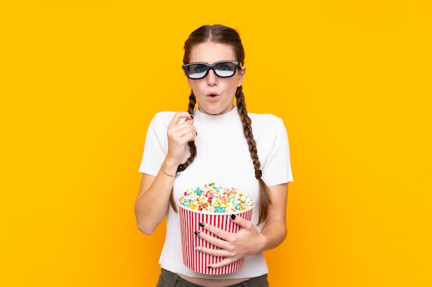 Young woman with popcorns over isolated wall