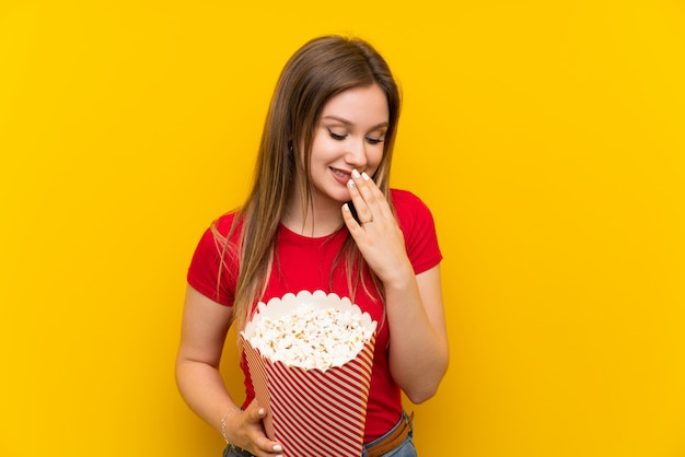Young woman with popcorns over pink wall smiling a lot