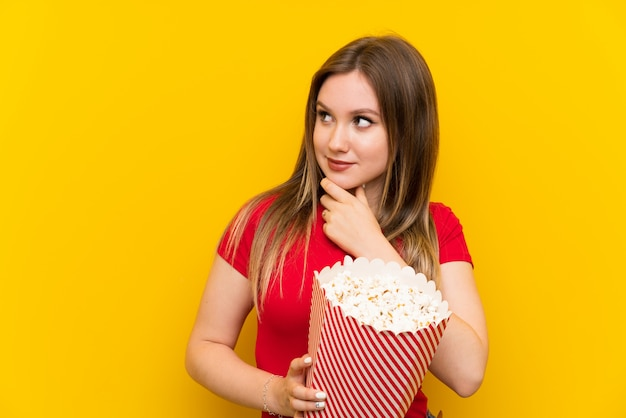 Young woman with popcorns over pink wall thinking an idea