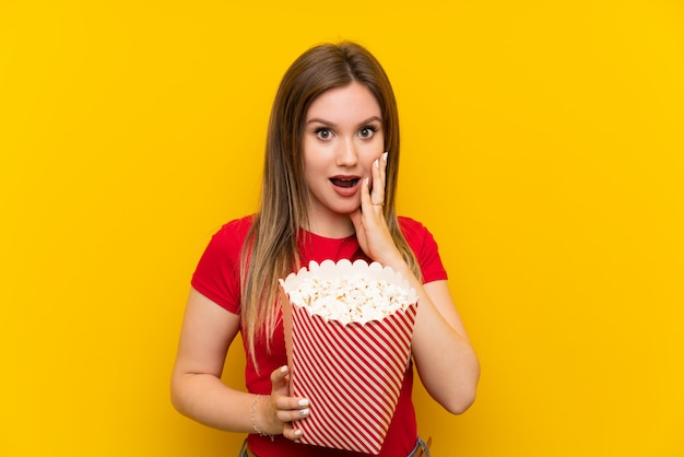 Young woman with popcorns over pink wall with surprise and shocked facial expression