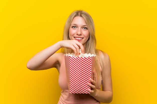 Young woman with popcorns over pink wall