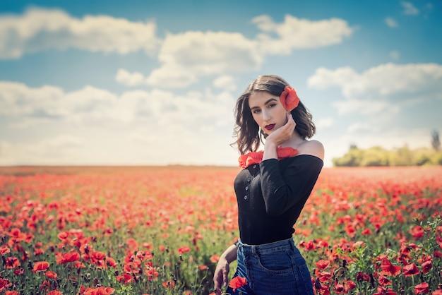 Молодая женщина с цветами мака в летний день поля