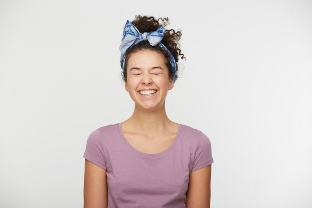 캐주얼 티셔츠와 세련된 머리띠를 입은 긍정적 인 표현을 가진 젊은 여성