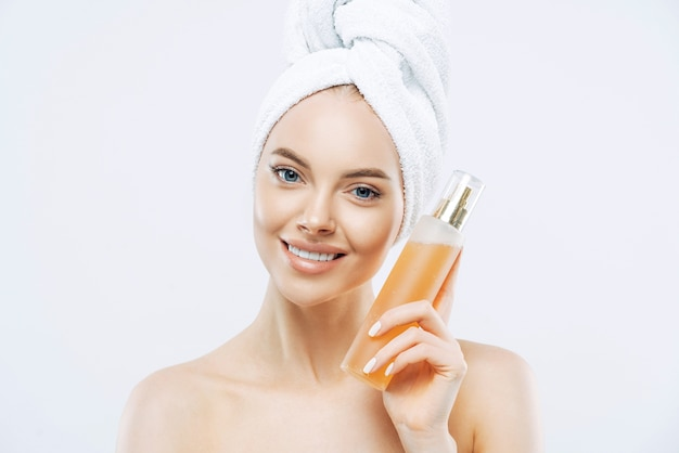Young woman with positive smile, holds big bottle of aromatic perfume with flower odor