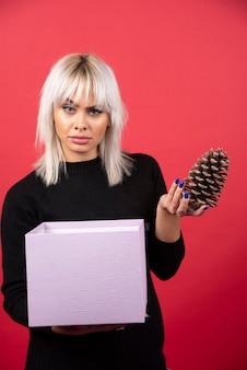현재 빨간색 배경에 큰 pinecone를 들고 젊은 여자. 고품질 사진
