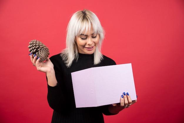Giovane donna con il presente che tiene una grande pigna su uno sfondo rosso. foto di alta qualità