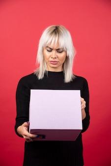 Giovane donna con presente su uno sfondo rosso. foto di alta qualità