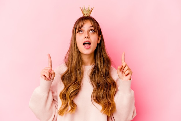 Young woman with princess crown isolated pointing upside with opened mouth
