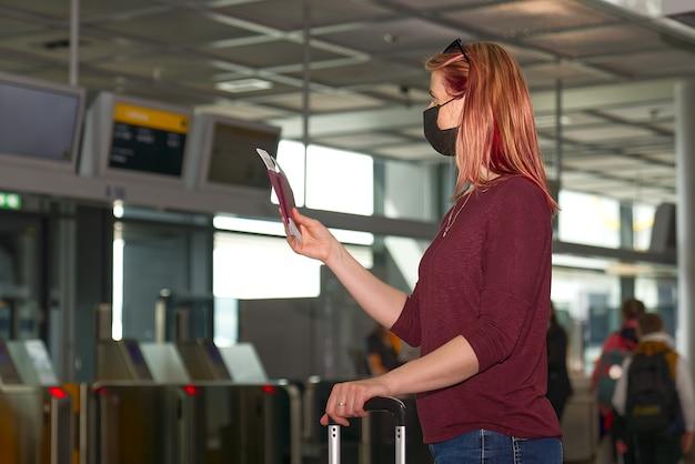 Молодая женщина с паспортом защитной маски и авиабилетами в международном аэропорту