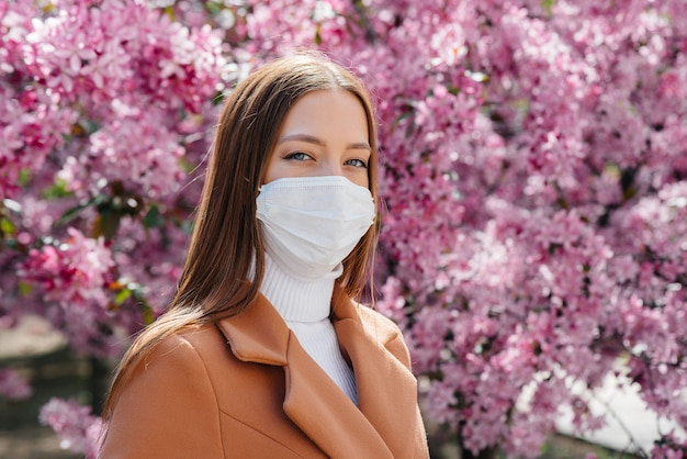 Young woman with protective mask and brown coat in cherry tree garden
