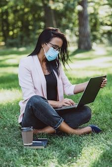 屋外で作業しながら公共の公園でラップトップを使用して保護マスクを持つ若い女性。