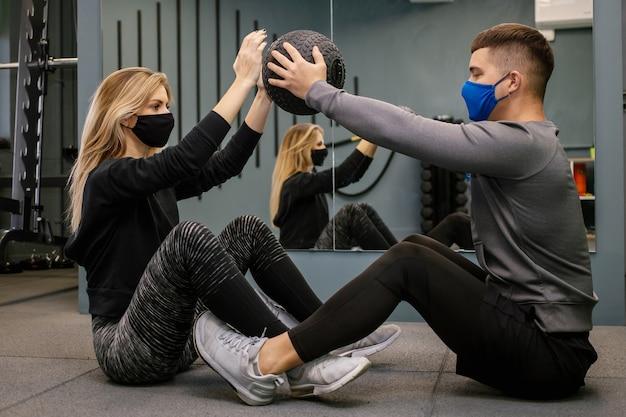Covid-19 유행성 기간 동안 체육관에서 개인 트레이너와 함께 운동하는 보호 마스크를 가진 젊은 여자. 그녀는 아령으로 근육을 펌핑하고 있습니다. 소프트 포커스