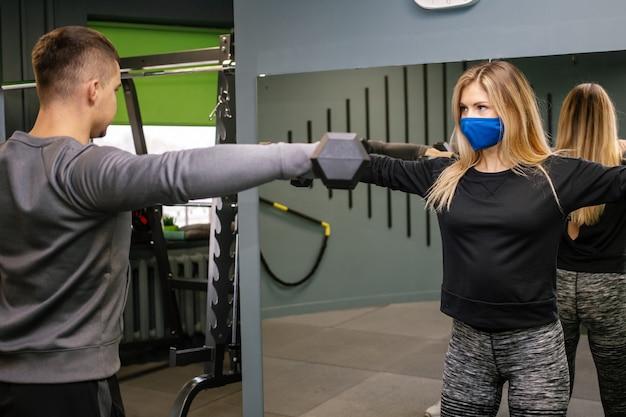 Covid-19 유행성 기간 동안 체육관에서 개인 트레이너와 함께 운동하는 보호 마스크를 가진 젊은 여자. 그녀는 아령으로 근육을 펌핑하고 있습니다.