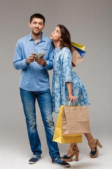 購入と灰色の壁にお金を置く男の若い女性