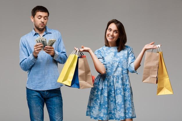 Giovane donna con gli acquisti e soldi della tenuta dell'uomo sopra la parete grigia