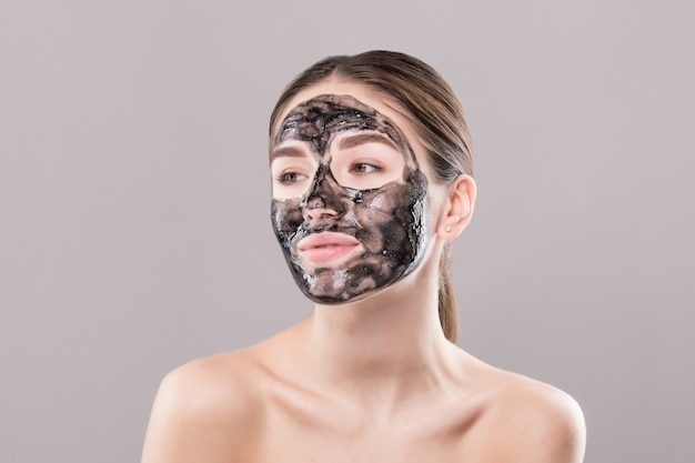 Young woman with purifying black mask on her face isolated on white wall