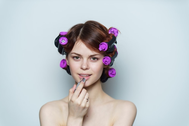 Young woman with purple curlers on her head naked shoulders gray background