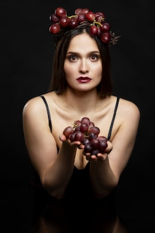 Young woman with purple grapes. beautiful brunette in the gothic style. black background.