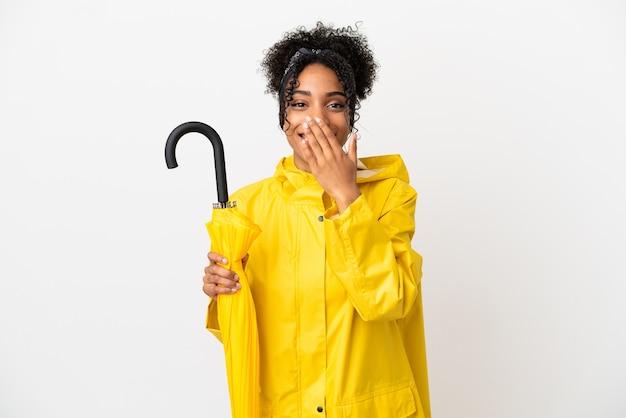 防雨コートと白い背景で隔離の傘を持つ若い女性幸せと笑顔の手で口を覆う