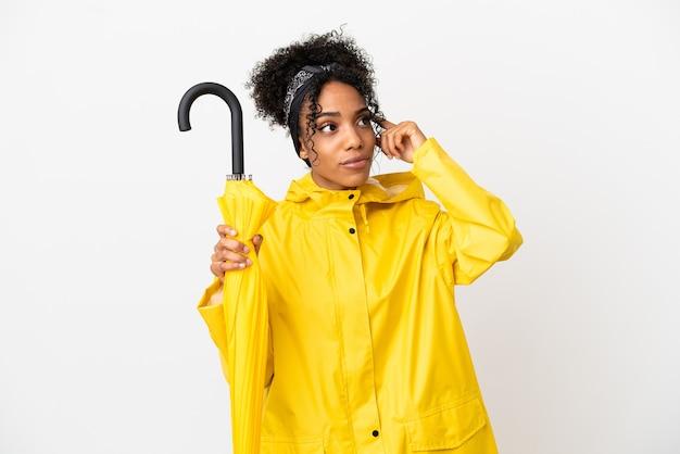 Молодая женщина с непромокаемым пальто и зонтиком на белом фоне с сомнениями и мышлением