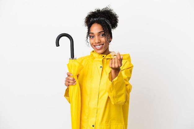 Молодая женщина с непромокаемым пальто и зонтиком на белом фоне делает денежный жест