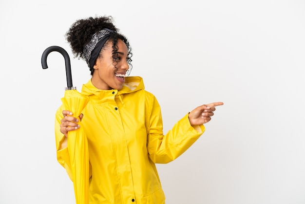 Молодая женщина с непромокаемым пальто и зонтиком на белом фоне, указывая пальцем в сторону и представляя продукт