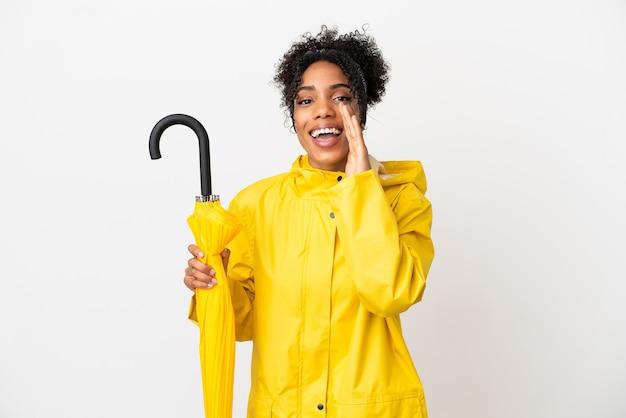 Молодая женщина с непромокаемым пальто и зонтиком на белом фоне кричит с широко открытым ртом