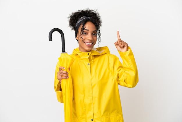 Молодая женщина с непромокаемым пальто и зонтиком на белом фоне показывает и поднимает палец в знак лучших