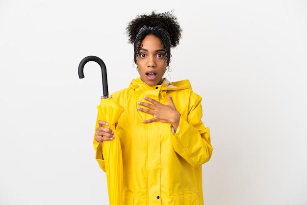 防雨コートと白い背景で隔離の傘を持つ若い女性は、右を見ながら驚いてショックを受けました