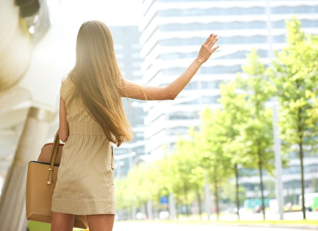Young woman with raised arm waving for taxi