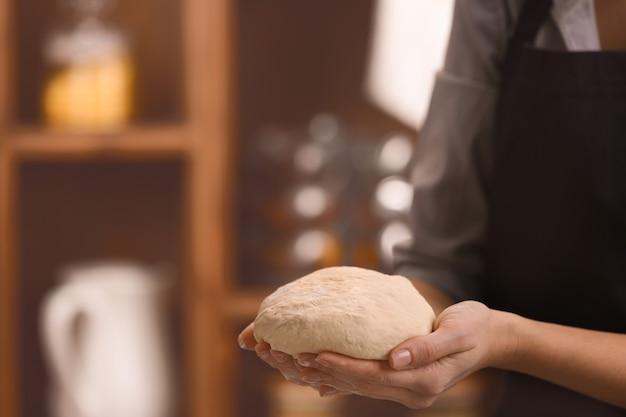 Молодая женщина с сырым тестом на кухне