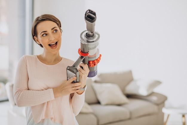 充電式掃除機を自宅で掃除する若い女性