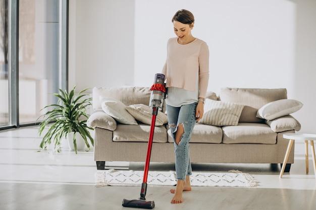 충전식 진공 청소기 집에서 청소와 젊은 여자