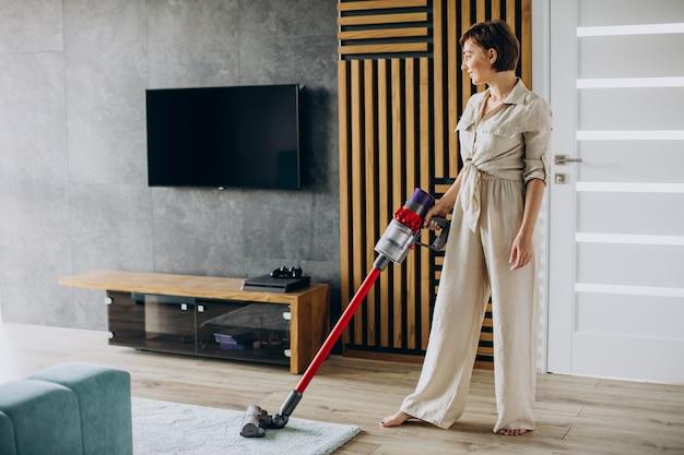 집에서 충전식 진공 청소기로 청소하는 젊은 여성