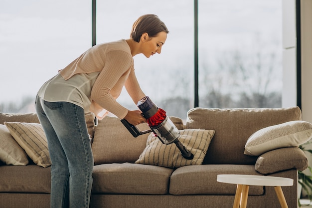 Giovane donna con aspirapolvere ricaricabile che pulisce a casa
