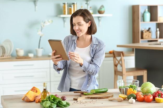 キッチンで料理のレシピ本を持つ若い女性